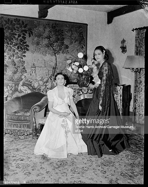 Lillian Murdocks Berry wearing light colored gown and Cordella Wharton wearing dark gown with large flower on bodice and lace shawl posed next to...
