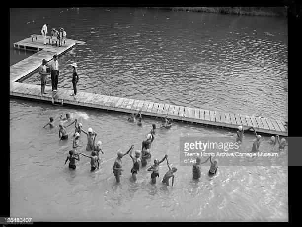 Group of boys and girls standing in water holding hands beside dock with boy wearing bathing suit and light colored hat standing on dock at Camp...