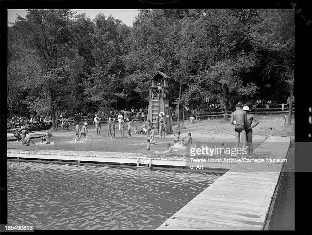 Boys and girls swimming in lake while lifeguards William Phillips and Clarence L Robinson look on at Camp Weldon Johnson Beaver County Pennsylvania...