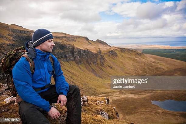 man sits contemplating on isle of skye scotland - western isles stock pictures, royalty-free photos & images