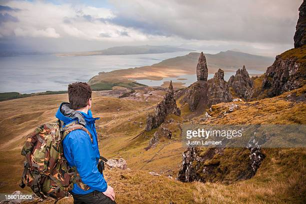 MAN LOOKS AT OLD MAN OF STORR ON THE ISLE OF SKYE,
