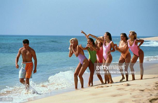 WOMEN WHISTLING AT MAN ON BEACH