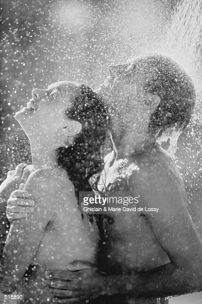 couple showering outdoors in black and white - couples showering stock pictures, royalty-free photos & images
