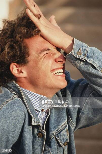 YOUNG MAN IN DENIM JACKET WITH HAND ON HEAD