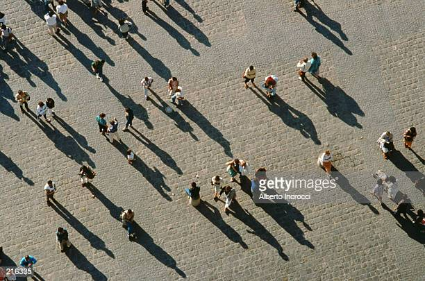 AERIAL OF CROWD WALKING WITH SHADOWS CAST
