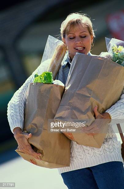 WOMAN BALANCING BAGS OF GROCERIES