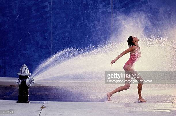 fire hydrant spraying water on woman - fire hydrant stock pictures, royalty-free photos & images