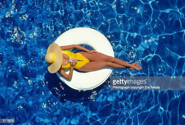 AERIAL VIEW OF A WOMAN IN HAT WITH DRINK IN POOL