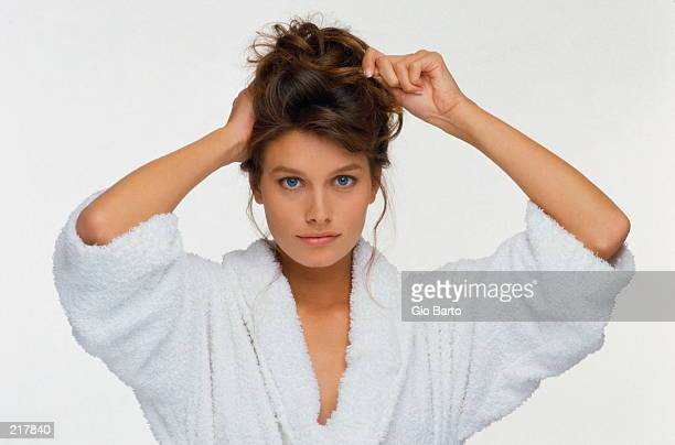 WOMAN IN ROBE PINNING UP HAIR