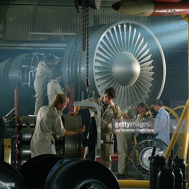 WORKERS IN AIRPLANE HANGAR