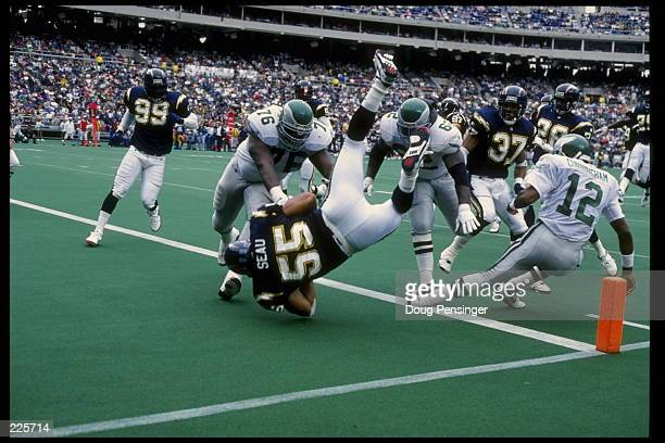 LINEBACKER JUNIOR SEAU OF THE SAN DIEGO CHARGERS IS UPENDED BY QUARTERBACK RANDALL CUNNINGHAM OF THE PHILADELPHIA EAGLES IN THE ENDZONE FOLLOWNING AN...