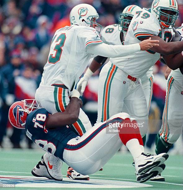 DEFENSIVE END BRUCE SMITH OF THE BUFFALO BILLS WRAPS UP QUARTERBACK DAN MARINO OF THE MIAMI DOLPHINS DURING THE SECOND QUARTER OF THE BILLS GAME...