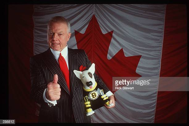 TELE VISION PERSONALITY DON CHERRY POSES IN FRONT OF THE CANADIAN FLAG WITH A BOSTON BRUIN DOG DURING A PHOTO SHOOT