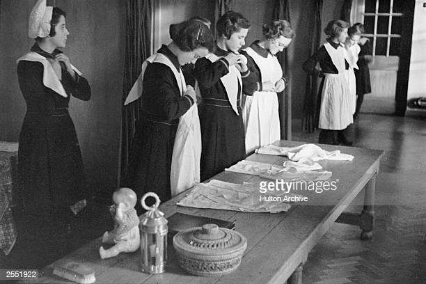 The girls take off their white aprons at a London foundling hospital 3rd May 1941 Picture Post 444 Foundling Hospital pub 1941