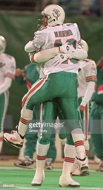 MIAMI DOLPHINS QUARTERBACK DAN MARINO CELEBRATES THE WINNING TOUCHDOWN OVER THE NEW YORK JETS IN THE ARMS OF MIAMI TIGHTEND RONNIE WILLIAMS DURING...
