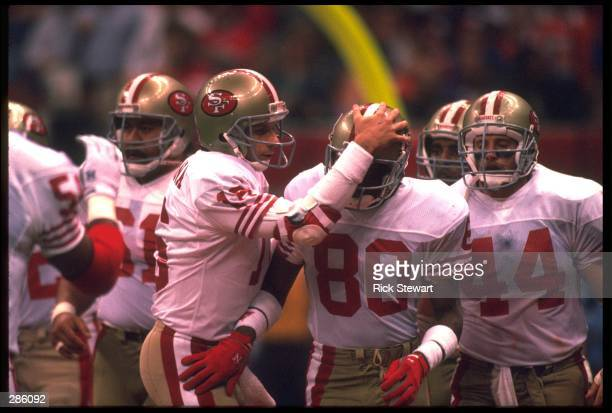 JOE MONTANA QUARTERBACK FOR THE SAN FRANCISCO 49ERS GREETS WIDE RECEIVER JERRY RICE DURING SUPER BOWL XXIV AS RUNNING BACK TOM RATHMAN AND OFFENSIVE...