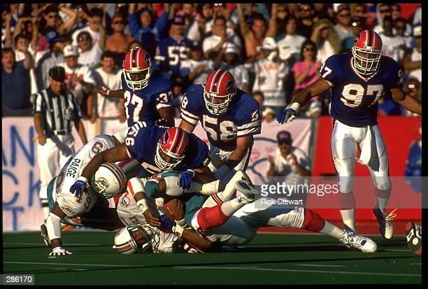 MARK HIGGS #21 RUNNING BACK OF THE MIAMI DOLPHINS GETS LITTLE HELP FROM TEAMMATE TONY PAIGE #49 AS HE IS CRUSHED BY BUFFALO BILLS LINEBACKERS DARRYL...