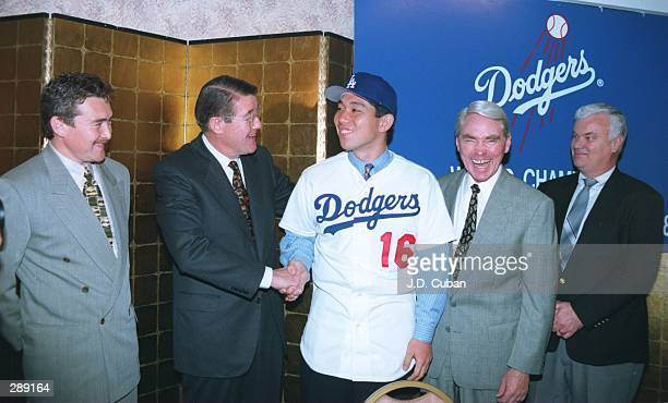 LOS ANGELES DODGERS'' PRESIDENT PETER O''MALLEY CONGRATULATES HIDEO NOMO OF JAPAN AFTER THE DODGERS SIGNED THE RIGHT HANDED PITCHER TO A MINOR LEAGUE...