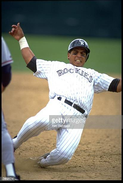 ANDRES GALARRAGA, FIRST BASEMAN FOR THE COLORADO ROCKIES, SLIDES INTO THIRD BASE DURING THEIR GAME AGAINST THE ATLANTA BRAVES AT MILE HIGH STADIUM IN...