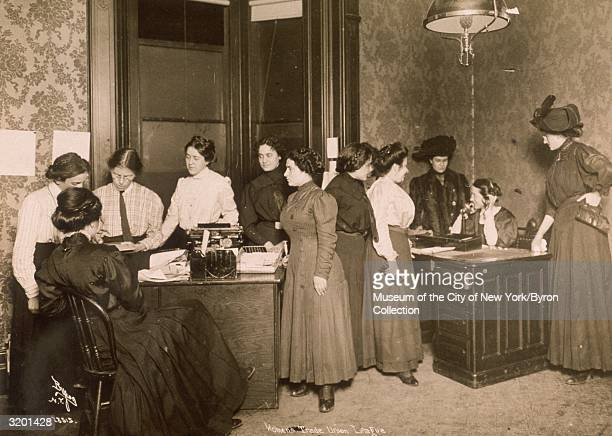 Fulllength view of an allfemale staff working while seated at and standing around desks in the Headquarters of the Women's Trade Union League of New...
