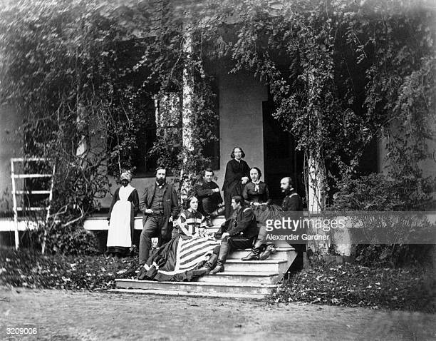 Three Union army soldiers pose on a front porch with three women a man and an elderly AfricanAmerican household worker in Pleasant Valley Maryland...