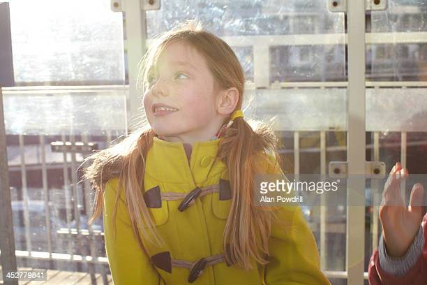 YOUNG GIRL SMILING AT BUS STOP PORTRAIT