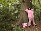 WOMAN DRESSED AS PIG IN FOREST