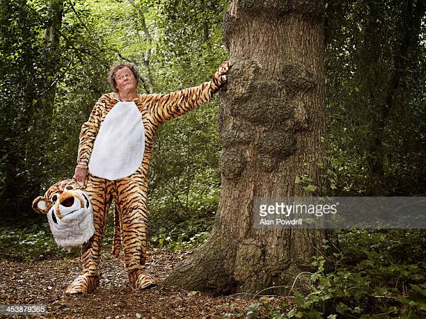 MAN DRESSED AS TIGER IN FOREST