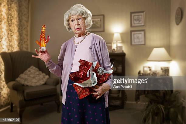 OLD WOMAN HOLDING A DILDO GIFT