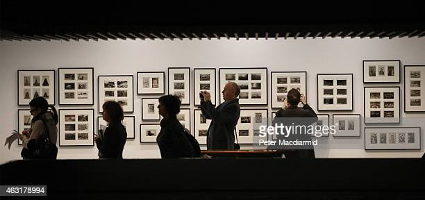 Visitors view and photograph Martin Parr's postcard collection on display at the Magnificent Obsessions The Artist as Collector exhibition at the...
