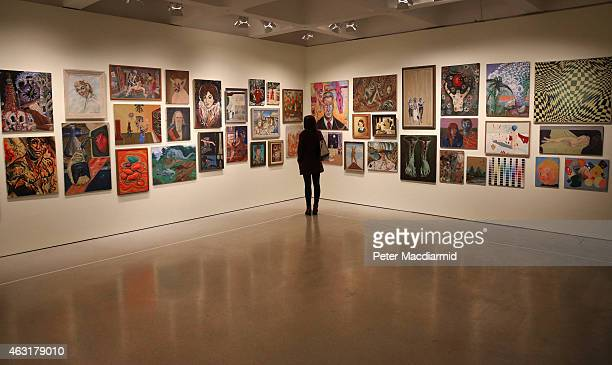 A visitor to the Magnificent Obsessions The Artist as Collector exhibition at the Barbican Art Gallery views Jim Shaw's thrift store paintings...
