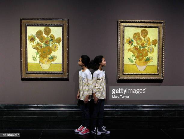 Twins Ella and Eva pose in front of two versions of Van Gogh's 'Sunflowers' which are on display in a new exhibition at the National Gallery on...