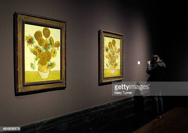 A photographer takes a picture of the display card beside one of Van Gogh's 'Sunflowers' which are on display in a new exhibition at the National...