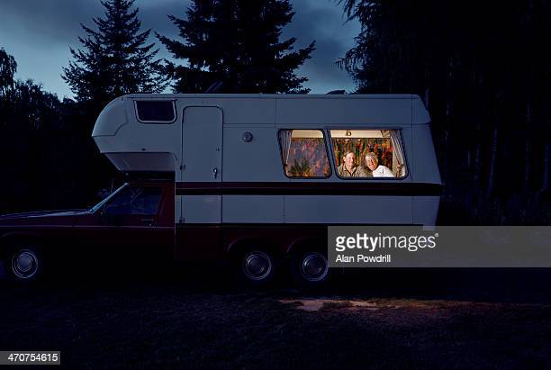 ELDERLY COUPLE SITTING INSIDE CAMPER VAN