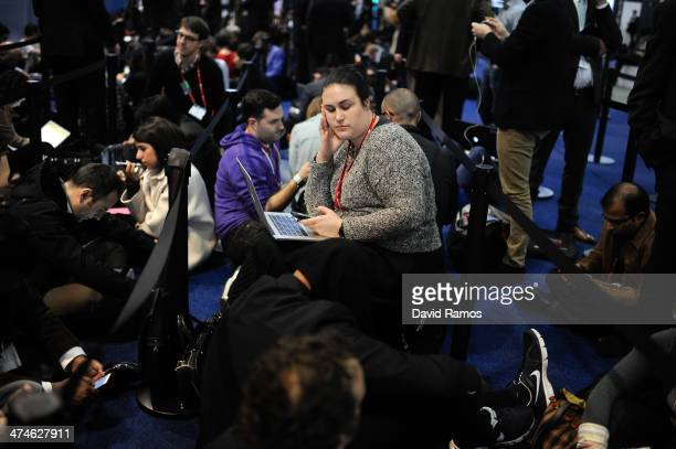 Visitors stand in a queue to see the CoFounder Chairman and CEO of Facebook Mark Zuckerberg during the first day of the Mobile World Congress 2014 at...