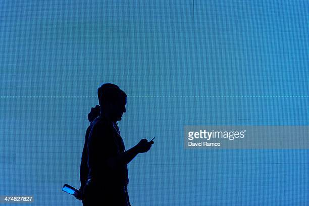 Visitors walk past a giant screen during the second day of the Mobile World Congress 2014 at the Fira Gran Via complex on February 25 2014 in...