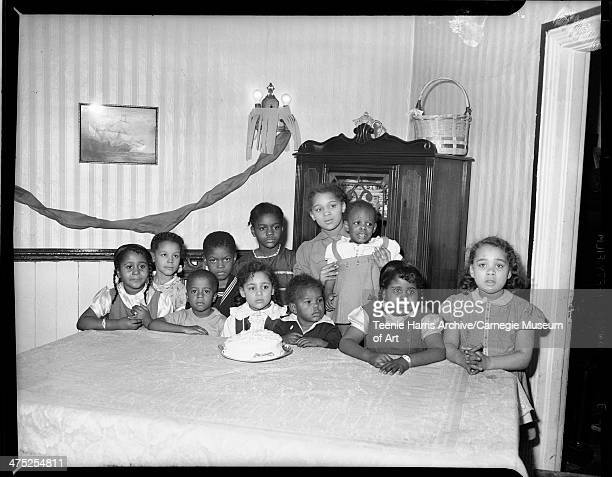 Group portrait of birthday party from left front row Joyce Barnett Clyde Barnett Mary Ann Scott William Dorsey standing behind his birthday cake...
