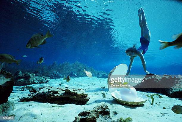 WOMAN SWIMMING UNDERWATER WITH PEARL