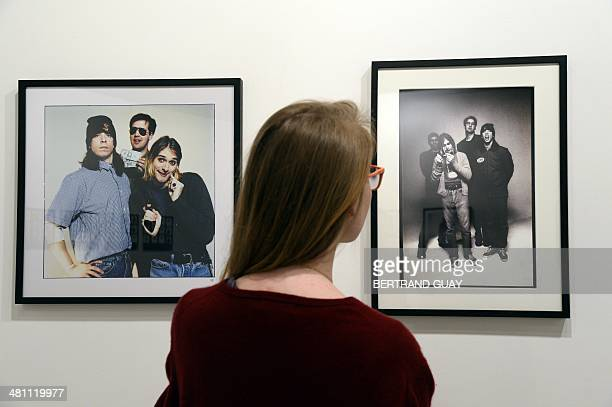 A woman looks at photos of late singer Kurt Cobain posing with members of his band Nirvana as part of the exhibition The Last Shooting on March 28...