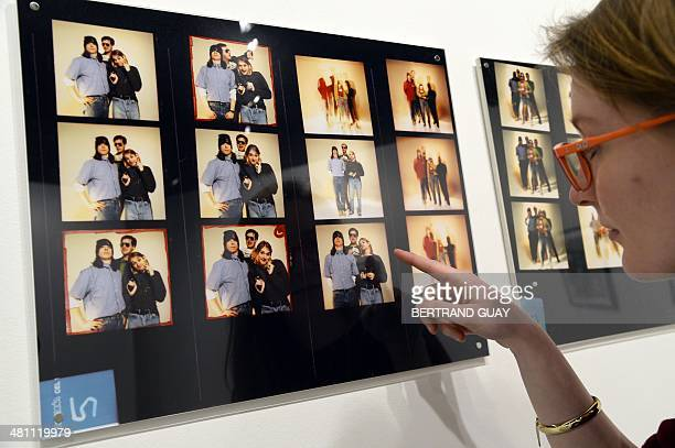 A woman looks at a blown up contact sheet of photos of late singer Kurt Cobain posing with members of his band Nirvana as part of the exhibition The...