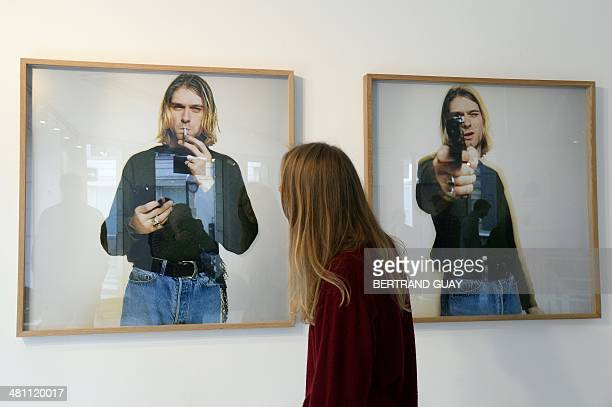 A woman looks at photos of late singer Kurt Cobain posing with a handgun as part of the exhibition The Last Shooting on March 28 2014 at the Addict...