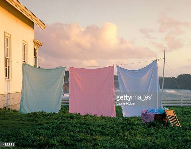 THREE COLORED SHEETS HANGING FROM LINE
