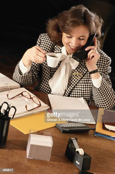 BUSINESSWOMAN AT DESK ON TELEPHONE