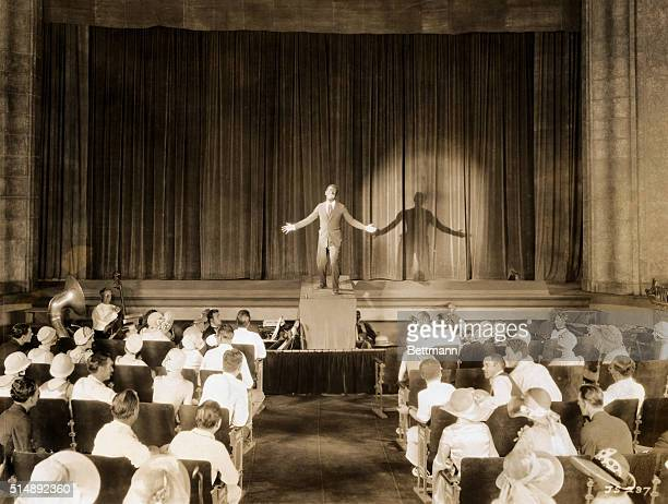 FAMOUS SCENE OF AL JOLSON IN THE 1927 WARNER BROS FILM THE JAZZ SINGER JOLSON IS ON STAGE IN BLACKFACE WITH SPOTLIGHT ON HIM ORCHESTRAL PIT IS ON...