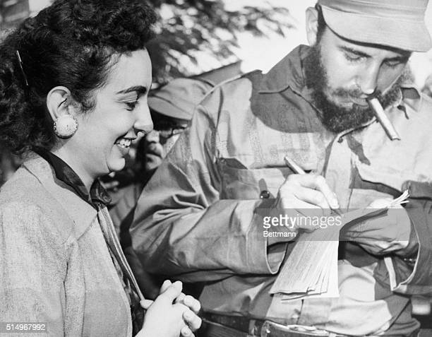 TAKING A MOMENT OUT DURING HIS TRIUMPHAL MARCH ACROSS CUBA REBEL LEADER FIDEL CASTRO GIVES AN AUTOGRAPH TO AN ADMIRER HERE JAN 5TH WHILE CUBANS...