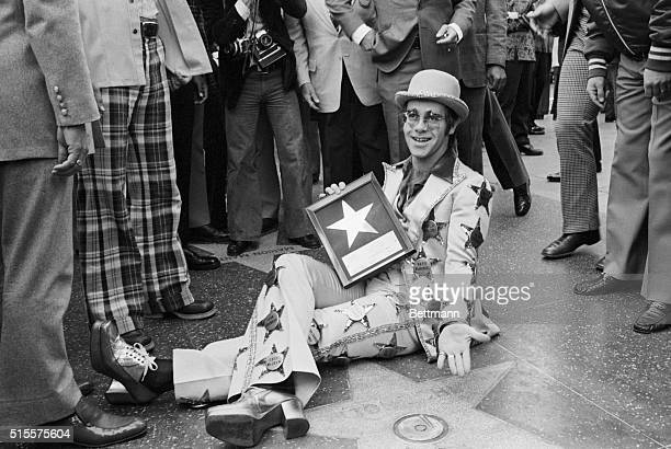 10/24/75-HOLLYWOOD: ROCK STAR ELTON JOHN RELAXES ON THE SIDEWALK OF HOLLYWOOD BLVD. AS HIS GOLD STAR WAS DEDICATED IN WALK OF FAME HERE 10/23. HE...