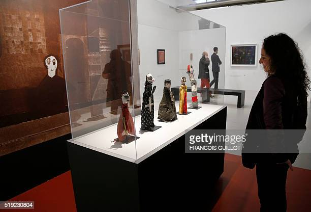 A visitor watches hand puppets made by German artist Paul Klee during the press preview at the Georges Pompidou Cultural and Art Centre on April 5...