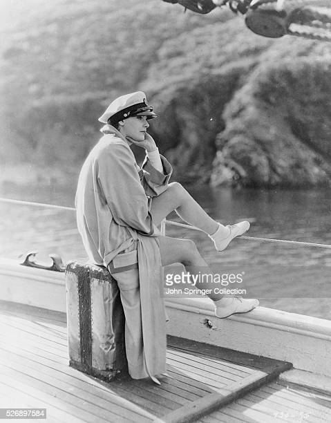 UNDATED PHOTO GARBO LOOKS PENSIVE WEARING A CAPTAIN'S HAT WHILE SITTING ON A BOX ON THE DECK OF A SHIP