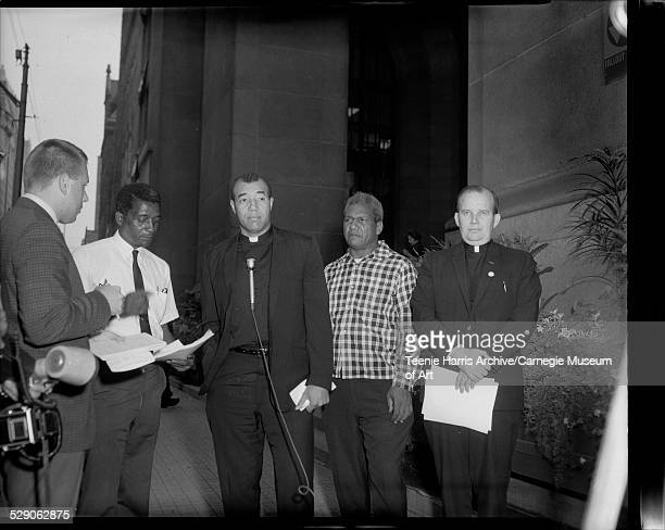Two unknown men Reverend Jimmy Joe Robinson William 'Bouie' Haden and Reverend Donald McIlvane outside large church or city building Pittsburgh...