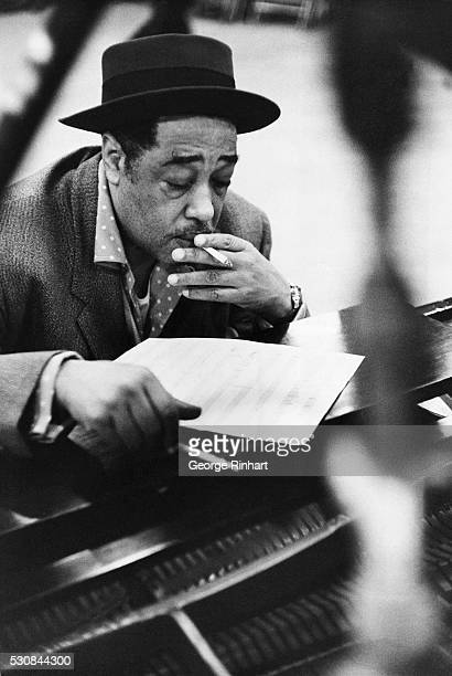 AMERICAN BANDLEADER AND COMPOSER SMOKES A CIGARETTE WHILE PERUSING SHEET MUSICUNDATED PHOTOGRAPH